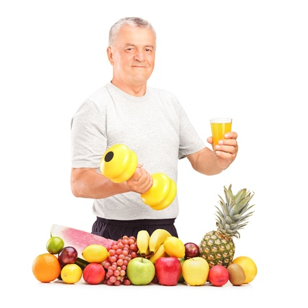 Mature man holding a dumbbell and glass of juice with pile of fruits and vegetables isolated on white photo