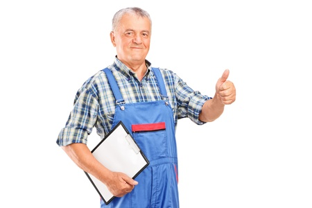 Mature mechanic holding a clipboard and giving a thumb up isolated on white background Stock Photo - 15038083