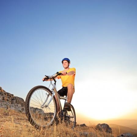 jinete: Persona que monta una bicicleta de montaña en una puesta de sol Foto de archivo