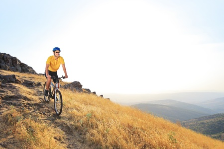 A young male riding a mountain bike on a sunset, Macedonia photo