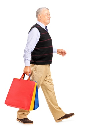 Full length portrait of a mature man coming back after shopping isolated on white background Stock Photo - 15255037