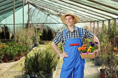 Young worker holding a basket full of flower pots and posing in a garden Stock Photo - 15255041