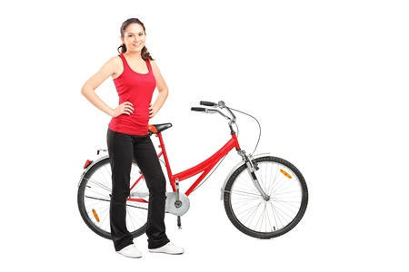 Full length portrait of a sporty girl posing next to a bike isolated on white background Stock Photo - 15255345