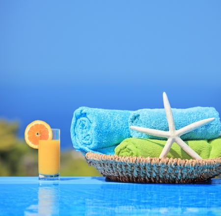 Orange juice, starfish and rolled up towels next to a swimming pool Stock Photo