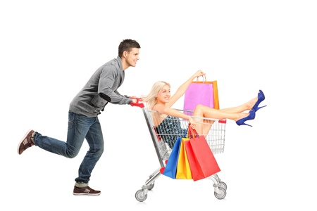 happy shopping: Person pushing a shopping cart, happy woman with bags in it, isolated on white background Stock Photo