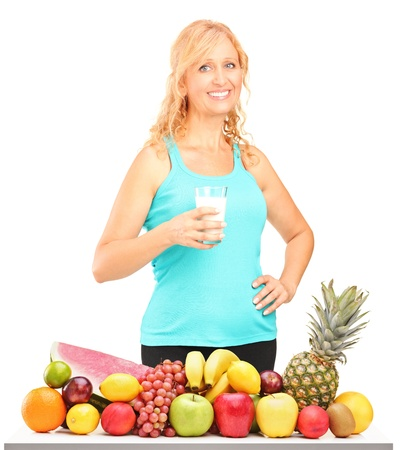 Woman holding a glass of milk with pile of fruits on a table, isolated on white background photo