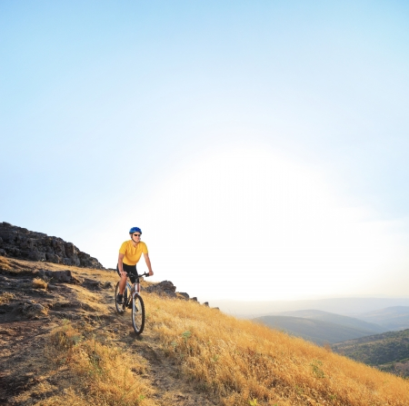 Young male riding a mountain bike on a sunset, Macedonia photo