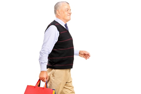 A mature man coming back after shopping isolated on white background Stock Photo - 15361430