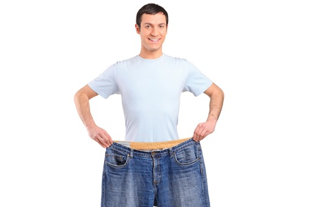 weight loss success: A weight loss male showing his old jeans isolated on white