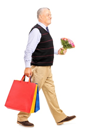 Full length portrait of a gentleman carrying gifts and bouquet isolated on white background photo