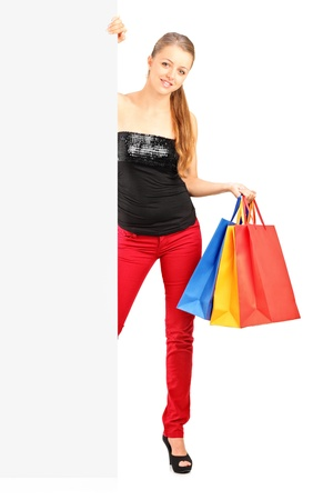advertisment: Full length portrait of a smiling woman holding a shopping bags behind a white panel Stock Photo