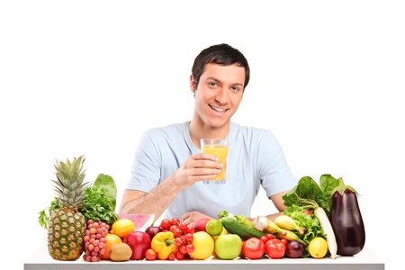 Handsome guy with glass of orange juice, on a table full of fruits and vegetables isolated on white background photo