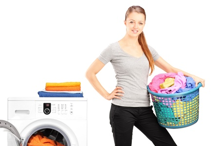 A smiling woman holding a laundry basket next to a washing machine isolated on white background photo