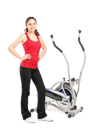 Young female posing next to a cross trainer isolated on white background photo