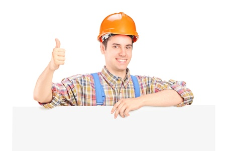 A happy male construction worker posing behind a blank panel giving thumb up photo