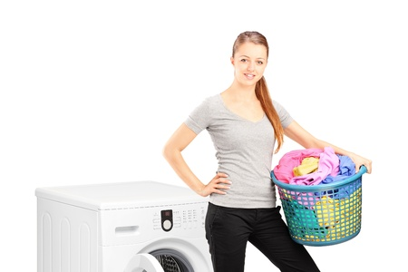 A smiling woman with laundry basket posing next to a washing machine isolated on white background photo