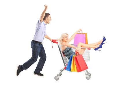 shopping cart isolated: Excited person pushing a shopping cart, happy woman with bags in it, isolated on white background