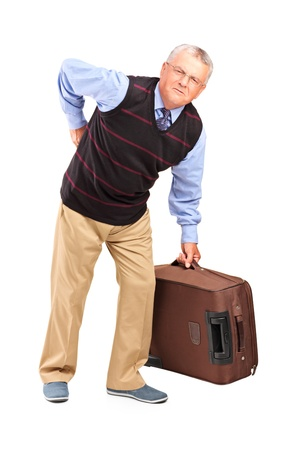 backpain: Full length portrait of a senior man lifting his luggage and suffering from a back pain isolated on white background Stock Photo
