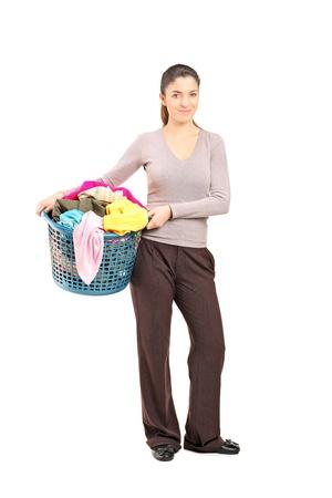 hamper: Full length portrait of a smiling female holding a laundry basket isolated on white background