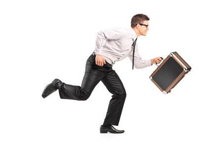 late 20s: Young businessman running with a briefcase isolated against white background