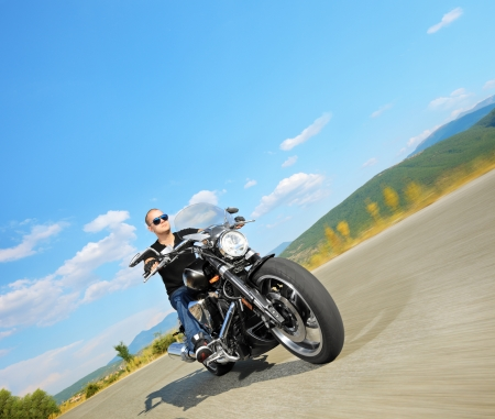 Biker riding a customized motorcycle on an open road photo