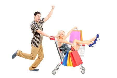 Excited person pushing a smiling woman with bags in a shopping cart isolated on white background 스톡 콘텐츠