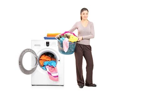 lavadora con ropa: Retrato de cuerpo entero de una mujer sonriente que sostiene una cesta de lavadero al lado de una lavadora aislada en blanco