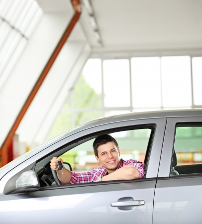 Happy male sitting in his automobile and holding a car key photo