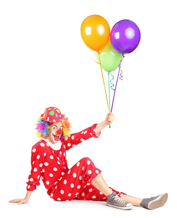 Smiling clown sitting and holding balloons isolated on white background Stock Photo - 15636203