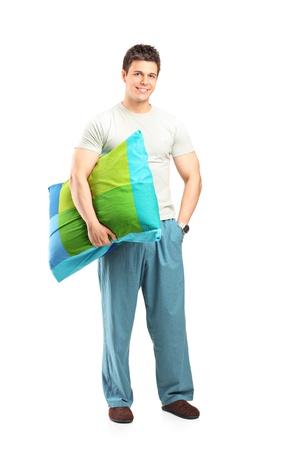 pijama: Retrato de cuerpo entero de un hombre sonriente en pijamas sosteniendo una almohada aislada en el fondo blanco