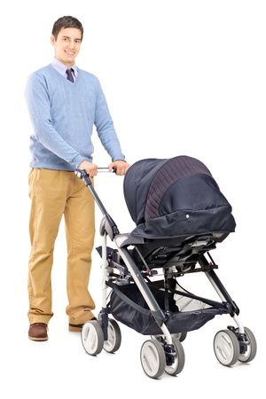 single father: Full length portrait of a young male pushing a baby stroller isolated on white background Stock Photo