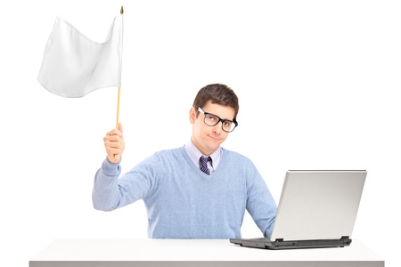 Sad man sitting with laptop and holding a white flag gesturing defeat isolated on white background photo