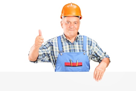 A male construction worker holding a panel and giving thumb up isolated on white background photo