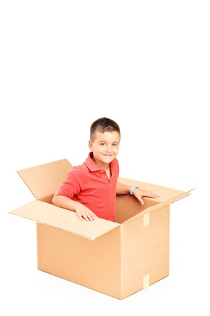 A smiling child in a cardbox isolated on white background photo
