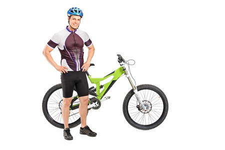 Full length portrait of a bicyclist posing next on a mountain bike isolated against white background