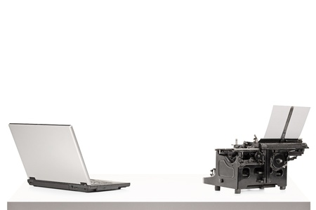 A laptop and old style typing machine on a table isolated on white background photo