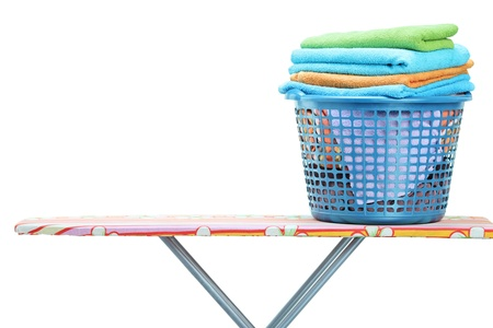 A laundry basket full of clothes on ironing board isolated on white background photo