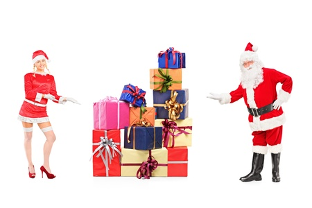Full length portrait of a male and female Santa Clauses offering presents isolated on white background photo