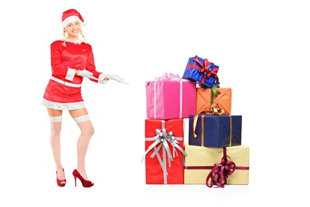 Full length portrait of a sexy female wearing santa costume and offering presents isolated on white background photo