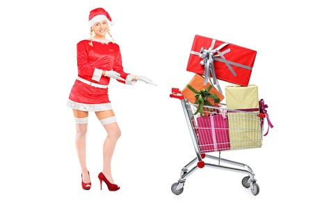 Full length portrait of a sexy woman wearing santa costume and showing a shopping cart full of presents isolated on white background  photo