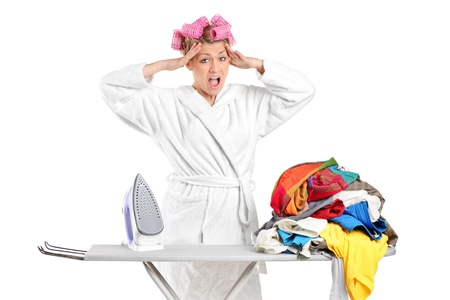 woman ironing: Annoyed housewife with ironing board and clothes isolated against white background