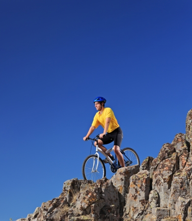 Person riding a mountain bike on rocks on a sunny day against a blue sky photo