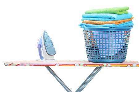 Studio shot of iron and laundry basket full of clothes on ironing board isolated on white background photo
