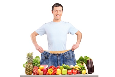 weight loss success: Portrait of a weight loss male showing his old jeans isolated on white
