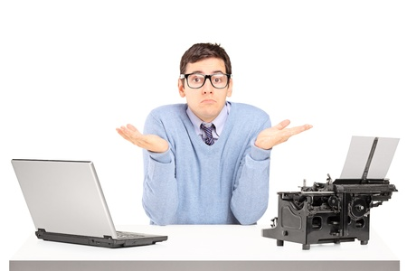 old man sitting: Confused young man with a laptop and typing machine on a table isolated on white background