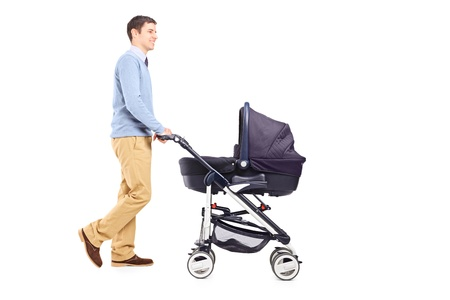 Full length portrait of a father pushing a baby stroller isolated on white background