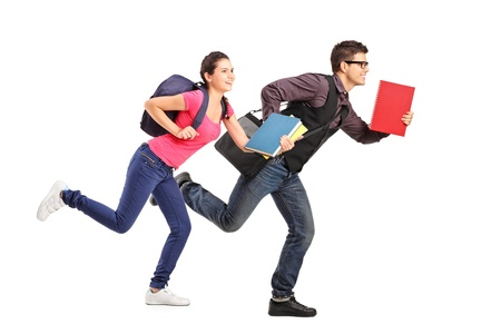 haste: Male and female students rushing forwards with books in their hands, focus on the boy Stock Photo