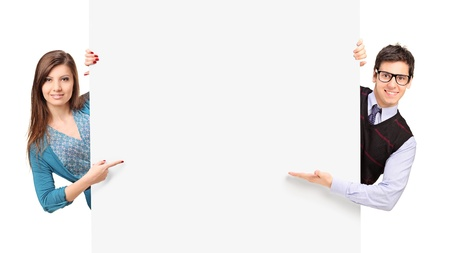 woman pointing: Man and female posing behind a blank panel isolated on white background Stock Photo