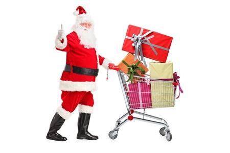 carretilla de mano: Papá Noel que empuja un carrito de la compra lleno de regalos y dando un pulgar hacia arriba aislados en fondo blanco