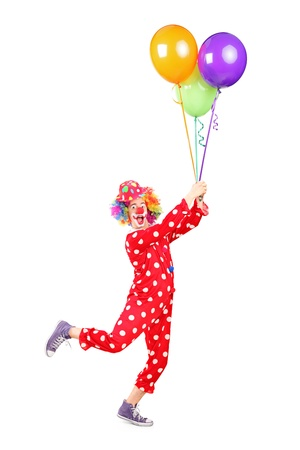 Full length portrait of a male clown holding balloons and flying isolated on white background photo